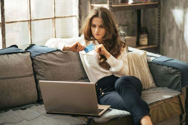 インターネットでクレジットカードを利用して買物する女性