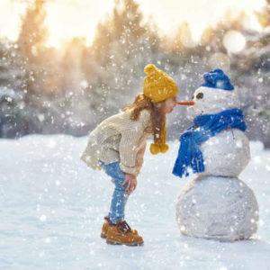 雪景色の中の雪ダルマと女の子